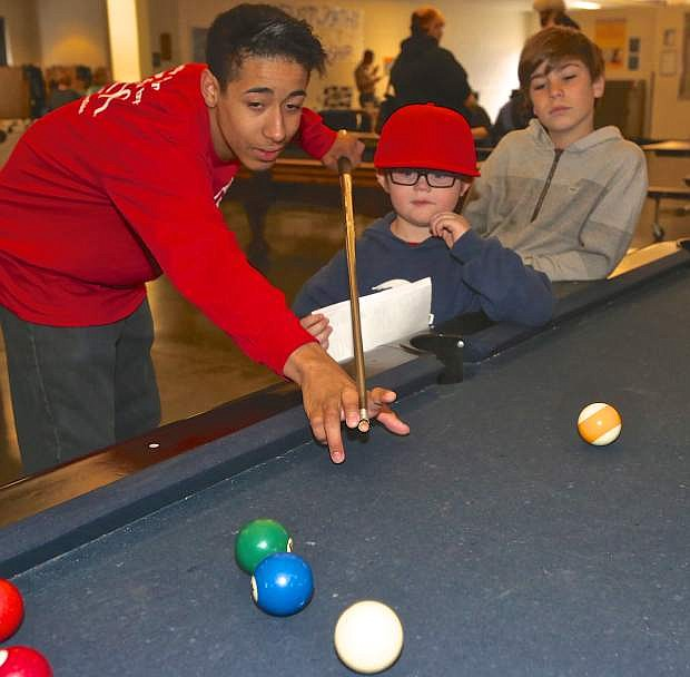 Staff member William Gershel plays pool with 5-year-old Caden Applewhite and 10-year-old Tegan Van Sickle Saturday at the Boys and Girls Clubs' kickoff event.