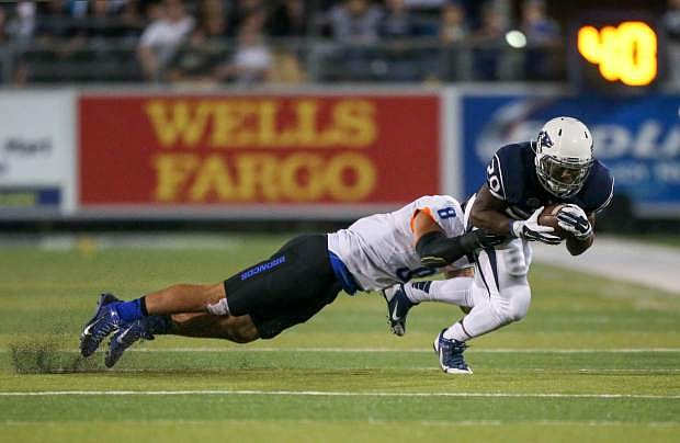 Nevada's James Butler (20) runs against Boise State's Kamalei Correa (8) the second half of an NCAA college football game in Reno, Nev., on Saturday, Oct. 4, 2014. Boise State won 51-46. (AP Photo/Cathleen Allison)