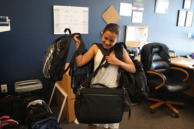 Eleven-year-old Laurel Czujko carries a bunch of backpacks filled with school supplies on Thursday. Almost 300 backpacks were filled with school supplies and hygiene items on Thursday at the Navy recruiting station for Carson City students. The backpacks will go to all schools in the Carson City School District as well as Capital City Circles and Child Protective Services. Soroptimist International of Carson City and Platinum Plus Salon & Spa sponsor the annual fundraiser.