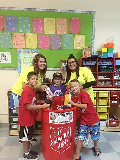 From the left, Cruz Gonzales, Recreation Lead Lindsey McElfish, first grader Rhyker Ricks, Recreation Aide Supervisor Sierra Fowzer, and second grader Chase Gonzales add school supplies to a Salvation Army donation bin.