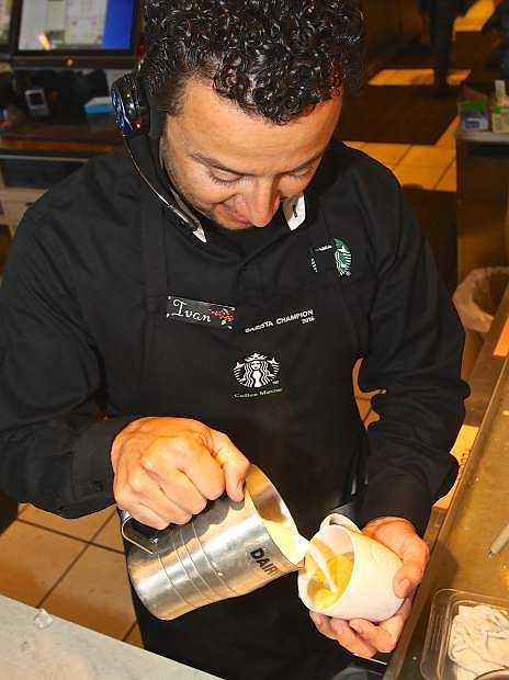 Ivan Rizo-Pineda pours milk into a flat white latte Wednesday at the north Starbucks in Carson City.
