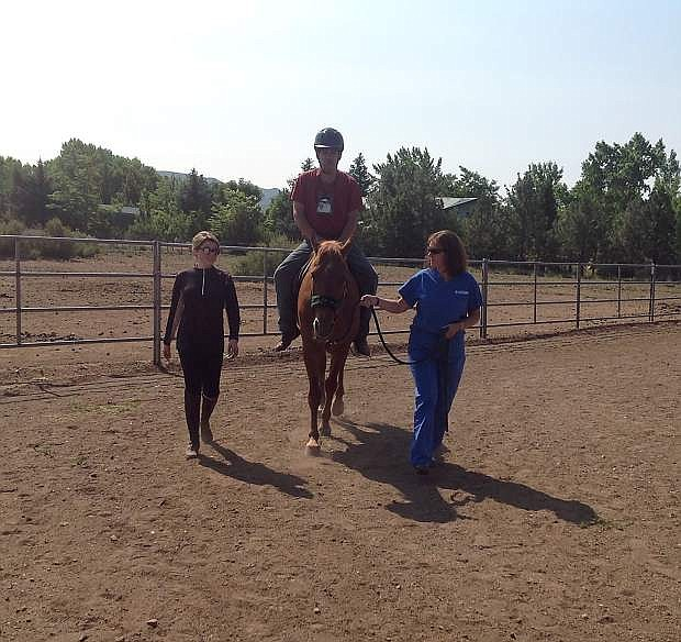 Michael, a veteran, rides Rugar June 26 at the Sierra Therapeutic Equestrian Program, STEP, arena in Washoe Valley. Michael is assisted by volunteers, Lexi, on the left, and Lynn, on the right.