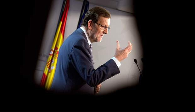 Spanish Prime Minister Mariano Rajoy gestures while speaking during a media conference after an EU summit in Brussels on Friday, Oct. 25, 2013. Migration, as well as an upcoming Eastern Partnership summit, topped the agenda in Friday's meeting of EU leaders. (AP Photo/Virginia Mayo)