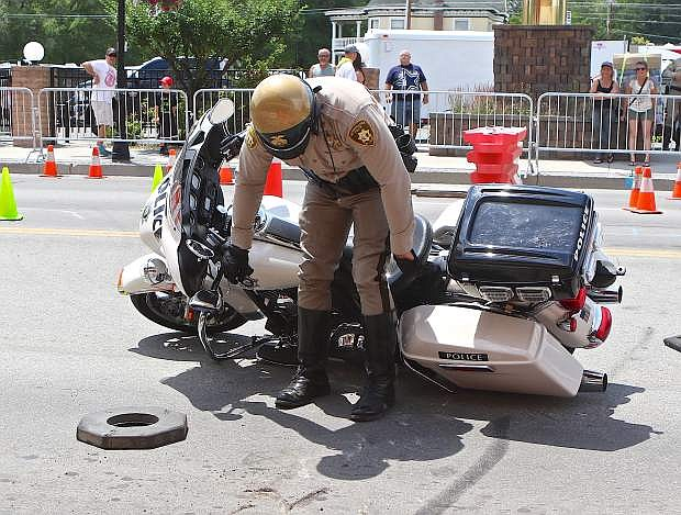 Las Vegas Metro Police Officer Jared Pribyl drops his Harley during competition downtown Saturday.