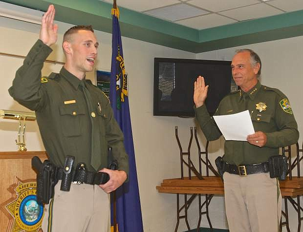 New Deputy Sheriff Cody Bindley takes his oath from Carson City Sheriff Ken Furlong Friday.