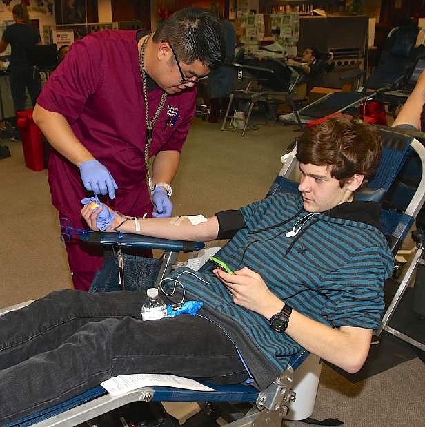 A member of United Blood Services draws blood from first-time donor  Logan Smedes, 16, Thursday afternoon at the Carson High library during the National Honor Society's blood drive.