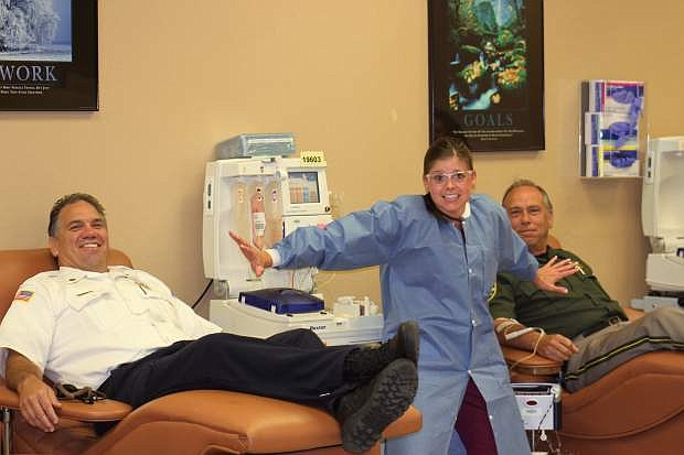 """A nurse keeps the peace as Fire Chief Bob Schreihans and Sheriff Ken Furlong """"battle"""" to donate blood for the United Blood Services in Carson City. Both the Sheriff's Office and the Fire Department will be participating in the Battle of the Badge blood drive on June 30."""