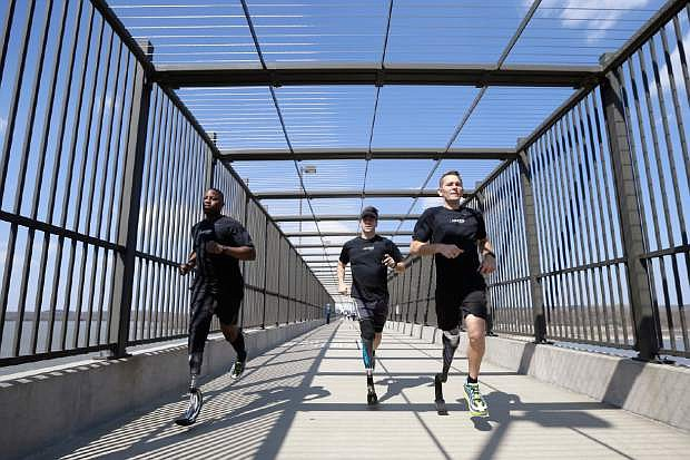 In this photo taken March 29, 2014, amputee marathon runners Andre Slay, left, Chris Madison, center, and Jeff Glasbrenner train on a footbridge aver the Arkansas river in Little Rock, Ark. (AP Photo/Danny Johnston)