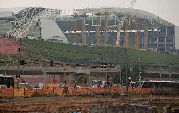 A buckled metal structure sits on a part of the Itaquerao Stadium in Sao Paulo, Brazil, Wednesday, Nov. 27, 2013. The accident that resulted in the death of at least two workers, occurred when a construction crane crashed into a 500-ton metal structure that in turn cut through the outer walls of the venue, destroying rows of seats and slamming into a massive LED panel that runs across the stadium's facade. The stadium is slated to host the 2014 World Cup opener. (AP Photo/Andre Penner)