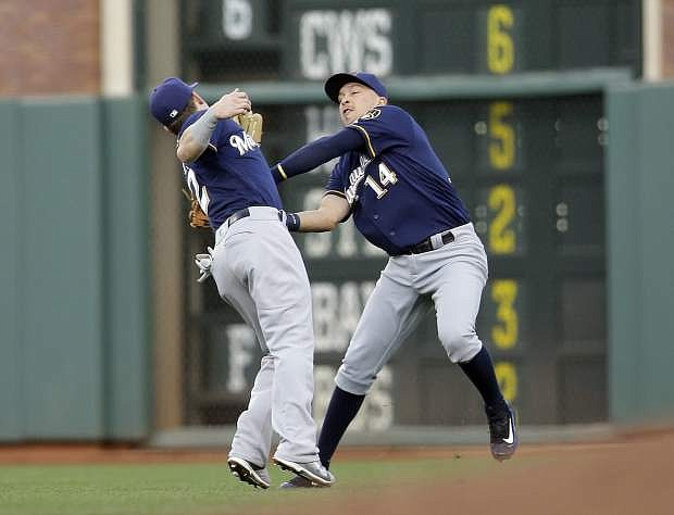 Milwaukee Brewers right fielder Hernan Perez (14) collides with second baseman Scooter Gennett while chasing a pop fly by San Francisco Giants' Gregor Blanco during the second inning of a baseball game Tuesday, June 14, 2016, in San Francisco. Blanco got a double on the play. (AP Photo/Marcio Jose Sanchez)