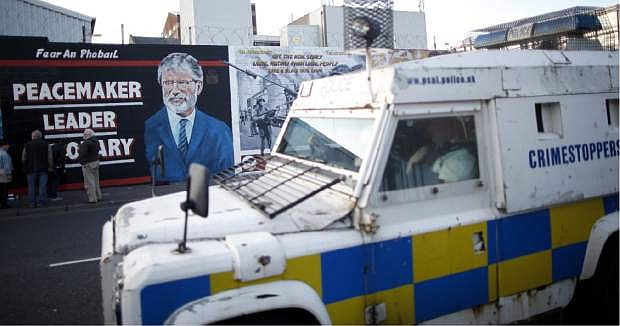 A police armoured vehicle passes a newly painted mural of Gerry Adams on the Falls Road, West Belfast, Northern Ireland, Northern Ireland, Friday, May, 2 2014.  Police continue to question the Sinn Fein leader Gerry Adams at Antrim police station about the 1972 murder of Jean McConville.  (AP Photo/Peter Morrison)