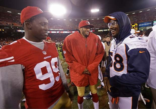 From left, San Francisco 49ers linebacker Aldon Smith, 49ers quarterback Colin Kaepernick, and Denver Broncos outside linebacker Von Miller talk at the end of their NFL preseason football game Thursday, Aug. 8, 2013, in San Francisco. Denver won the game 10-6. (AP Photo/Marcio Jose Sanchez)
