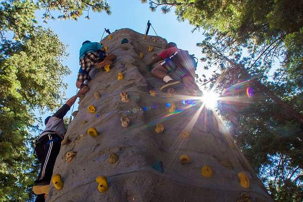 Campers at the Firefighters Kids Camp scale a rock climbing wall. The camp caters to children who have suffered from severe burn injuries.