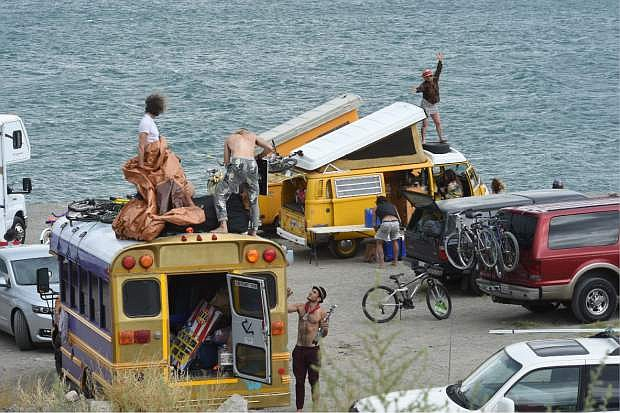 A woman dances on top of a van while other people set up camp on Blockhouse Beach at Pyramid Lake on Monday, Aug. 25, 2014, northeast of Reno, Nev. Thousands of Burning Man enthusiasts were on the outside looking in Monday after a rare batch of heavy rain forced organizers to temporarily close entry to the counterculture event in the desert 90 miles north of Reno. Many took advantage of the opportunity to camp at Pyramid Lake and made the best of the lake's beaches. (AP Photo/Reno Gazette-Journal, Tim Dunn)