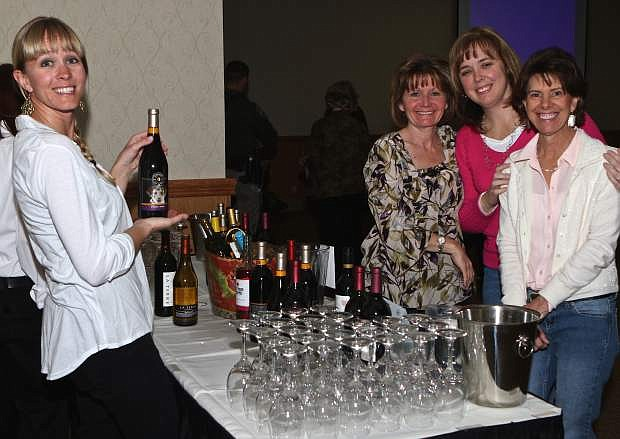 Laura Redmon serves some wine to Debbie Thrower, Sara Zaro and Bernadette Lissaline Saturday night at 'Woofs, Wine and Whiskers', a Carson Animial Services Initiative fundraiser for the new animal shelter in Carson City.