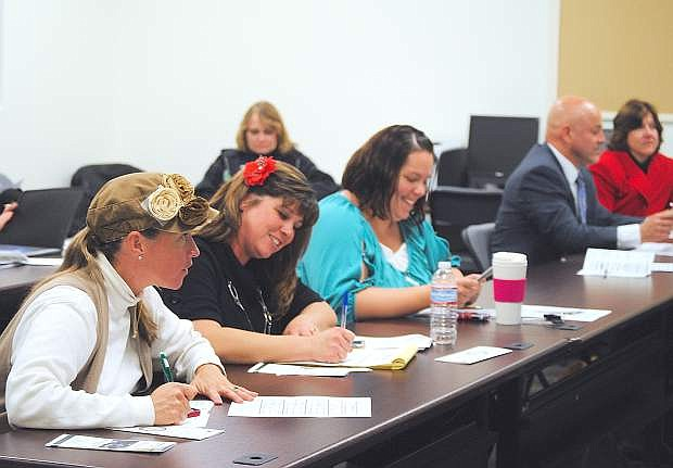 Attendees at a Churchill County School Board worskshop take notes during one of the sessions.