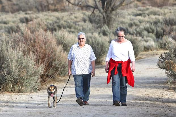 Sisters Eileen Dana of Carson and Terry Redmond of San Francisco take a walk with Eileen's dog Jake at Riverview Park Friday.