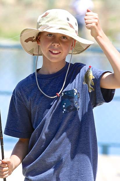 10-year-old Trevor Marlin displays his catch on a beautiful day at Baily Pond Friday.