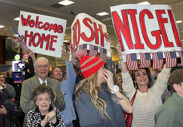 Family and friends, many of whom are from Carson City, wave signs welcoming home Chief Warrant Officer Josh Groth and 1Lt. Nigel Harrison.