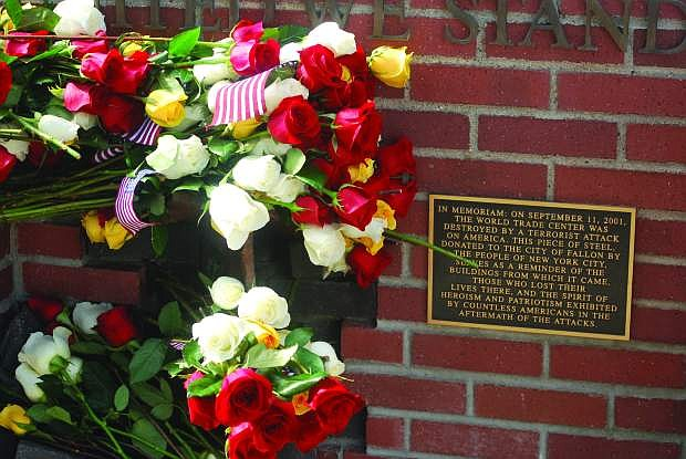 Flowers adorn a wall behind the Fallon City Hall  after a previous 9/11 ceremony remembered those who lost their lives on Sept. 11, 2001.