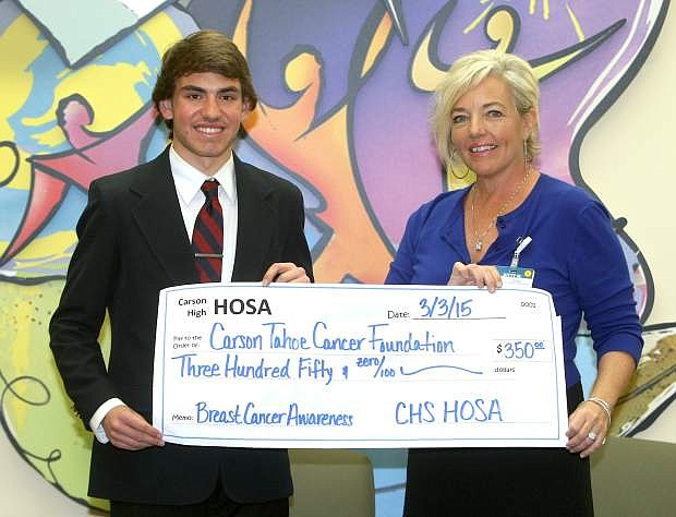 Carson High School senior Michael Leiken, who is president of the school's HOSA club presents a $350 check to Kitty McKay of the Carson Tahoe Cancer Center on Tuesday. Members of HOSA sold breast cancer awareness lanyards to raise money for breast cancer awarness and research.