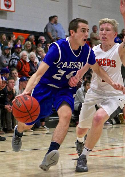Senator point guard Jared Rooker drives past Douglas' Dylan Pfaffenberger Friday night in a win against the Tigers in Minden.