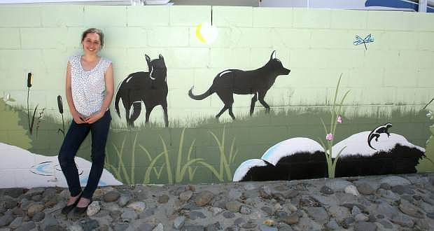 Carson High School senior Erica Gallegos leans against a mural she painted on a cinder block wall by the Fulstone Wetlands park.
