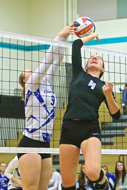 Carson's Maddie Jergesen (9) stuffs Reed's Annie Braun (4) at the net in a win over the Raiders at North Valleys High School last year.