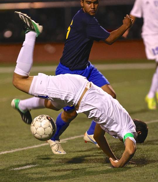 Senator Oscar Ventura is upended by a Reed player Wednesday night at Carson High.