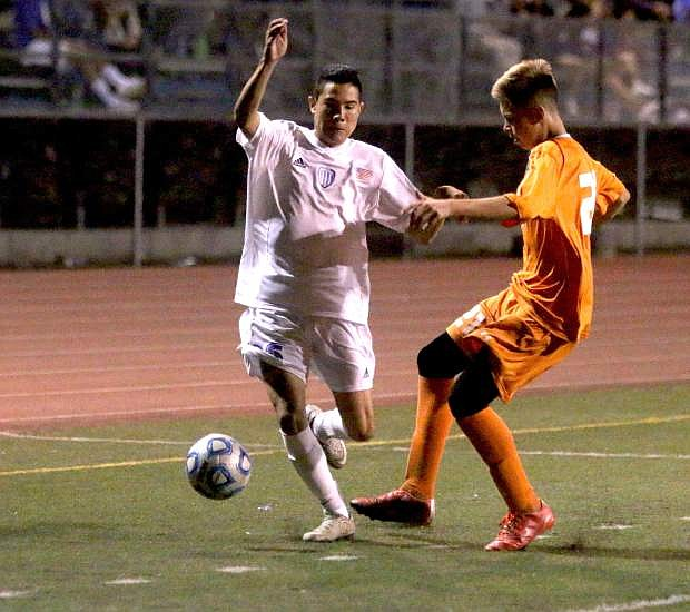 Carson's Rogelio Herrera battles with Douglas' Niklas Wegner for possesion Friday night.