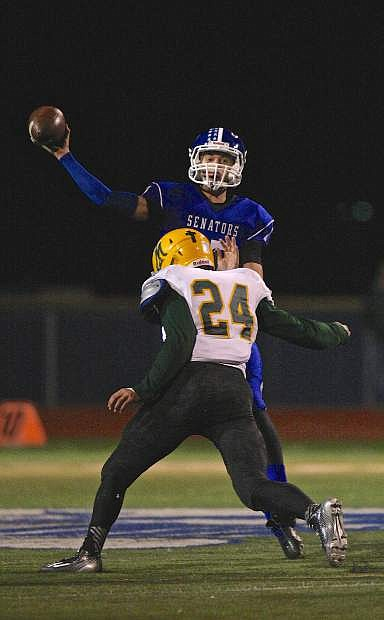 Carson QB Joe Nelson let's one fly just before getting hit by Manogue's Wes Farnsworth (24) Friday night at CHS.