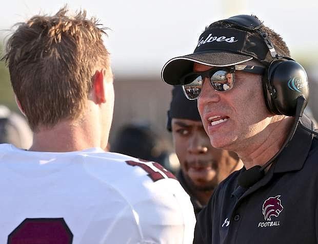 Desert Mountain offensive coordinator and retired Super Bowl and NFL MVP Kurt Warner talks to his quarterback Saturday night at Carson High.
