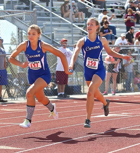 Athena Favero (left) takes the stick from a relay teammate last season at the state track meet in Las Vegas.