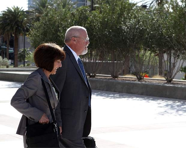 One-time political powerbroker Harvey Whittemore leaves the Lloyd George Federal Courthouse in Las Vegas, Wednesday, April 3, 2013. Whittemore was attending a hearing on whether to toss out the evidence in the campaign contribution case against him. The woman next to him is unidentified. (AP Photo//Las Vegas Review-Journal, Jerry Henkel)