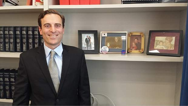 In this Jan. 14, 2015 photo, Nevada Attorney General Adam Laxalt poses in his office in Carson City, Nev. with photos of his family. Laxalt has been flying into headwinds from the time he announced his campaign for attorney general, so it was fitting that a blizzard hit central Nevada on the December day when he drove north to take office as the state's top lawman. (AP Photo/Michelle Rindels))
