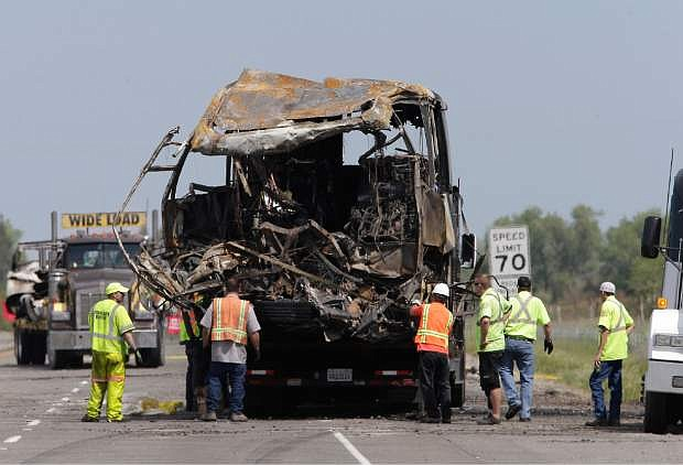 The burned out remains of a tour bus involved in a fiery crash with FedEx truck, sits on a flatbed truck before being taken from the scene, Friday April 11, 2014 in Orland, Calif.  Ten people were killed and dozens injured in the fiery crash between the truck and the bus carrying high school students on a visit to a Northern California College, Thursday.(AP Photo/Rich Pedroncelli)