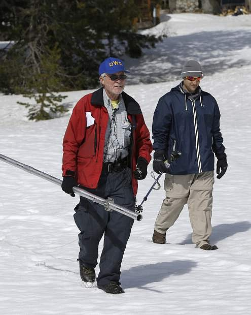 Frank Gehrke, left, chief of the California Cooperative Snow Surveys Program for the Department of Water Resources, accompanied by Brian Brown, of the Legislative Analysts office, cross a snow covered meadow to perform the third manual snow survey of the season at Phillips Station near Echo Summit, Calif., Tuesday, March 1, 2016.  State surveyors found Tuesday that a record-breaking warm, dry month of February ate away at what had been a well-above normal Sierra Nevada snowpack.  (AP Photo/Rich Pedroncelli)