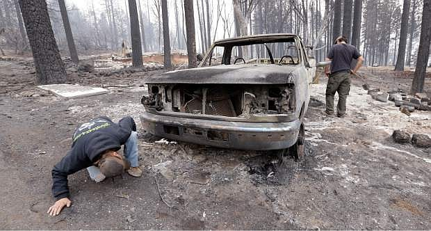 Joel Miller looks under the remains of the pickup truck of his son-in-law, Adam Bailey, right, next to the still-smoldering remains of Bailey's home Monday in Cobb, Calif. Bailey escaped the flames with his baby Saturday, just before flre roared through the neighborhood of about two dozen homes.