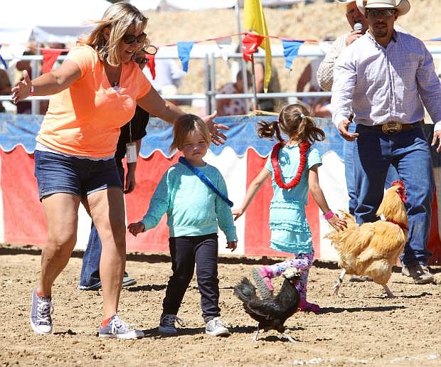 Jennifer, left, and three-year-old Julie Fleischmann of Minden near the finish line with their winning chicken in Virginia City Friday.