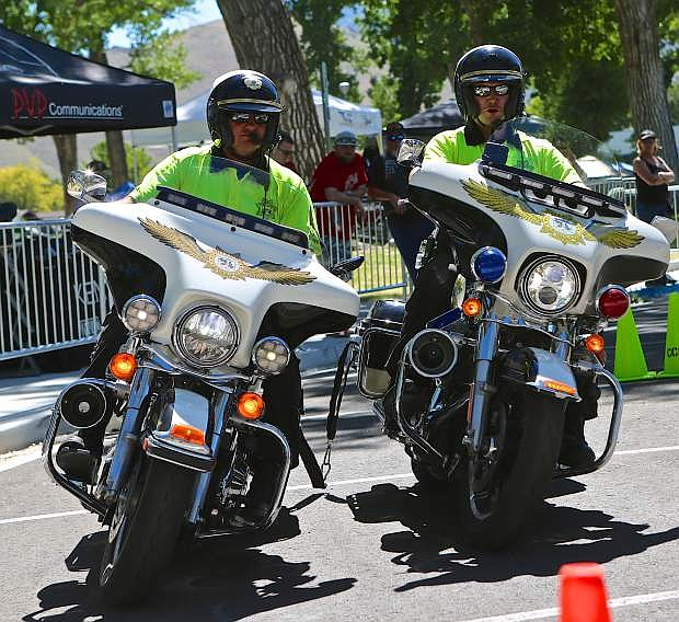 CCSO Motor Deputies Wayne Wheeler (left) and Joey Trotter finish a practice run for the 'Two-Man-Tether' event Friday during the Extreme Motor Officer Training Challenge in Mills Park.