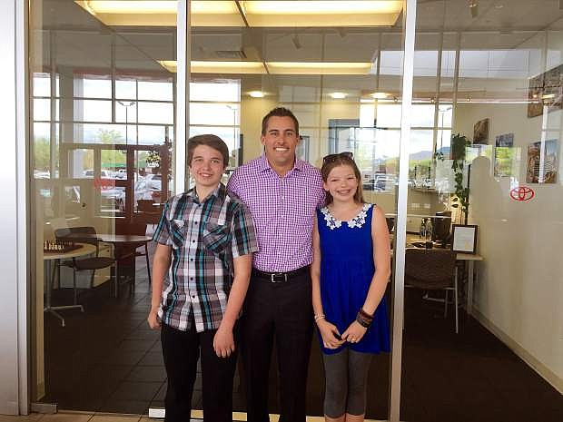 Sixth graders from Carson Montessori School visited local places of business on Career Day. Brady Dolan of Dolan Auto Group hosts sixth grade students Derrick Johnson and Jeslyn Stammer.