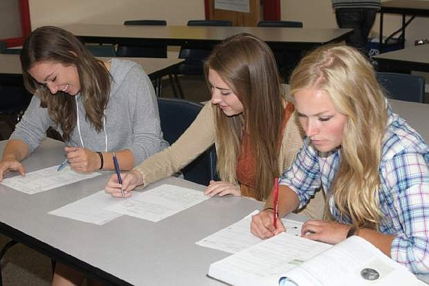 (L-R) Carson AP students Sarah Christl, Samantha Lowe and Abbey Dudley work on math problems at the high school Thursday.
