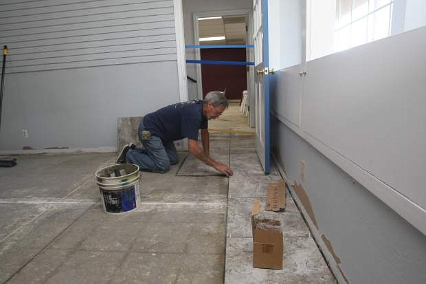 Mike Neally places new floor tile inside the Carson City Chamber of Commerce office.