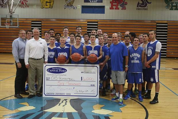 Tim Miiigan, general manager of Capital Ford and Cliff Sorensen director of Carson Auto Group present a $6,000 check to Coach Mendeguia and the Carson High School boys basketball team. The money will be used for travel and equipment,