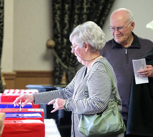 Bill Witt looks on as his wife Theresa votes in the GOP caucus at the Carson Nugget on Tuesday night.