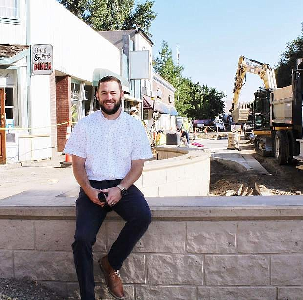 Carson City Engineering Manager Danny Rotter sits on one of the newly poured seat walls that will contain landscaping and serve as a place to rest.