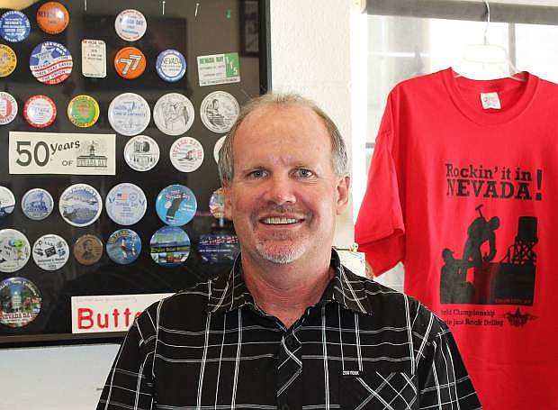 Nevada Day Executive Director Ken Hamilton stands in front of some of the collectible buttons produced annually along with T-Shirts available for sale at the Nevada Day Store, conveniently located at 108 W. Telegraph Street.