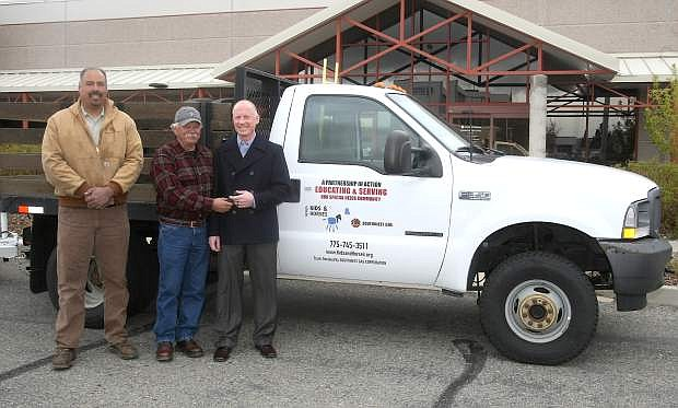 Southwest Gas Vice President, Northern Nevada Division Brad Harris, right, presents the keys to a Ford F-350 1-ton flatbed truck to Doug Brimm, director of Kids and Horses, a therapeutic riding center located in Minden on Tuesday.The truck will be used to transport hay and other bulky materials that are necessary to support the Kids and Horses Ranch. Looking on is Marcus Hernandez, district auto mechanic for Southwest Gas.