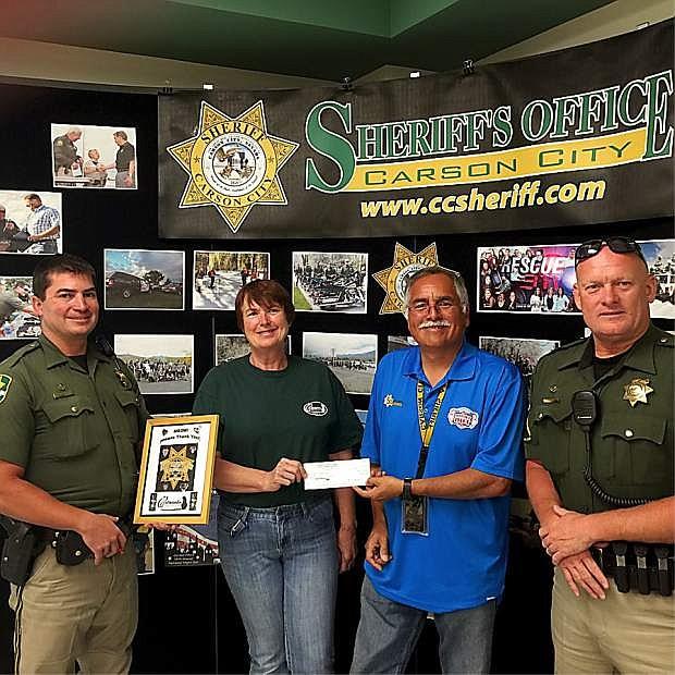 From left: Carson City Sheriff Deputy Matt Smith, Catmandu founder Linda Buchanan, Sgt. Scott McDaniel and Deputy Gary Denham at a check passing from the CCSO to Catmandu on Wednesday.