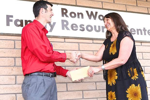 Save Mart Store Manager Chris Benson presents Joyce Buckingham, Exec. Director of the Ron Wood Family Resource Center, a $2031 check on Thursday.